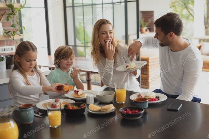 Caucasian family having food at dining table in a comfortable home.
