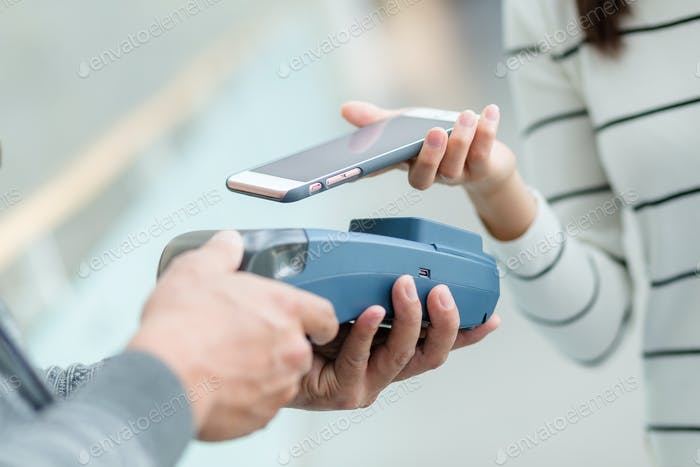 Woman using cellphone pay by NFC