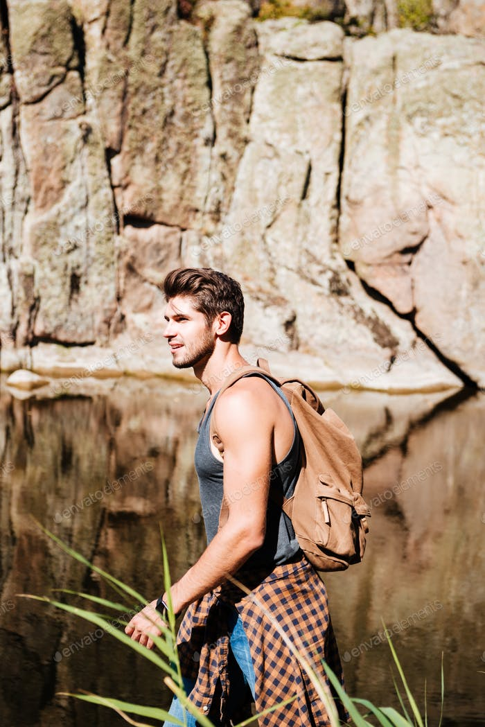 Portrait of an adventure man hiking wilderness mountain with backpack