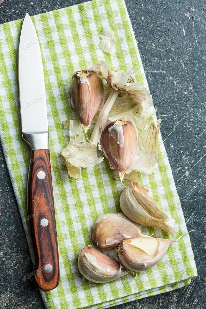 The fresh garlic with knife.