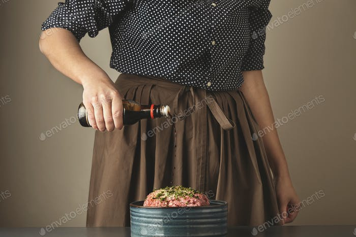 Women pours soy sause in minced meat
