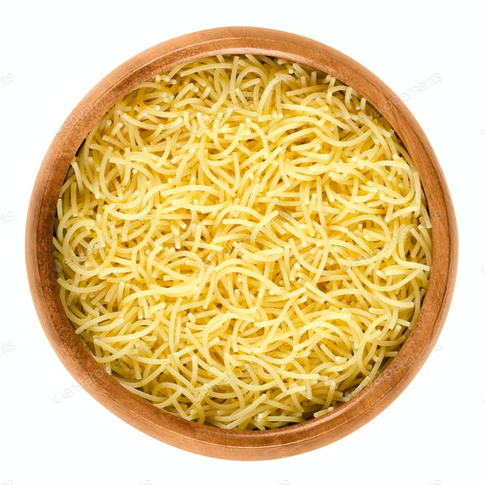 Filini short cut pasta in wooden bowl over white