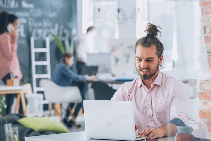 Smiling bearded corporate man using laptop