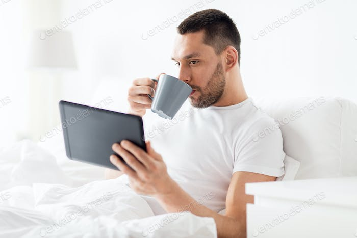 man with tablet pc drinking coffee in bed at home
