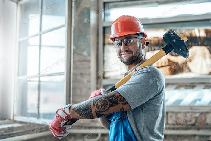 A construction worker stands by the window and holds a huge hammer