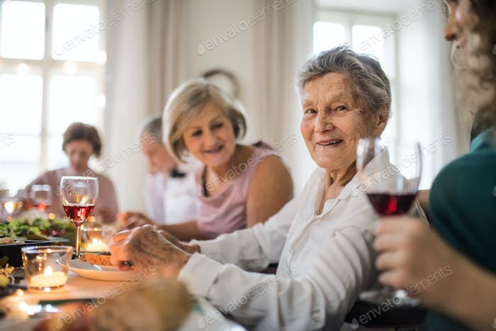 An elderly women with a family sitting at a table on a indoor family birthday party.
