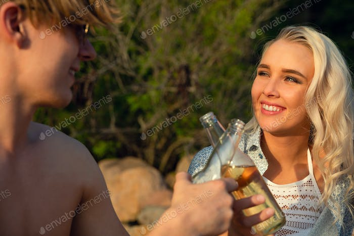 Smiling Young Couple Toasting Beer Bottles At Beach