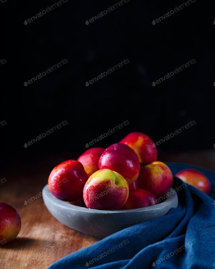 Eine Gruppe von bunten Nektarinen Früchten oder Pfirsich auf einem Teller
