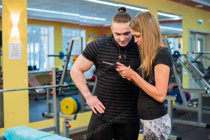 fitness, sport, exercising, technology and diet concept - smiling young woman and personal trainer