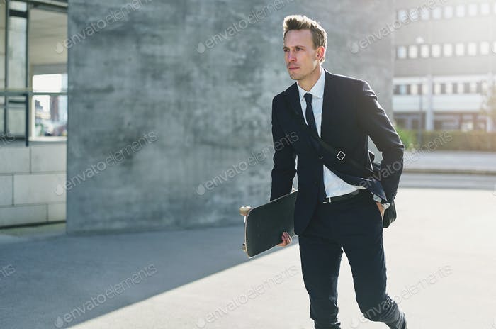 Confident handsome worker holding skateboard and walking