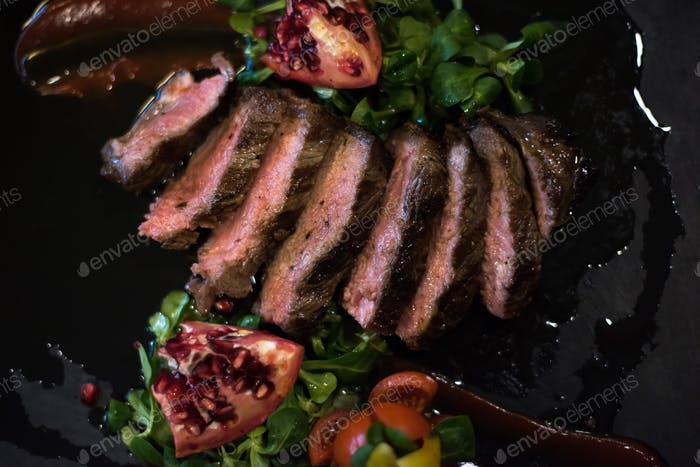 Juicy slices of grilled steak on wooden board