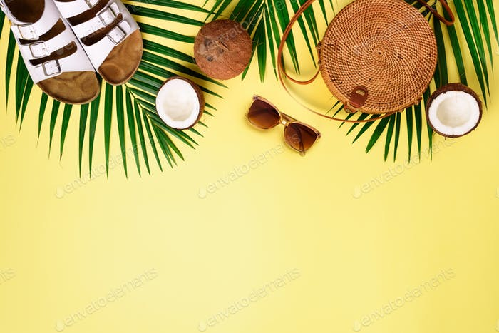 Round rattan bag, coconut, birkenstocks, palm branches, sunglasses on yellow background. Banner. Top