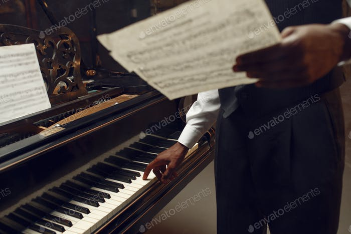 Black pianist with music notebook in his hands
