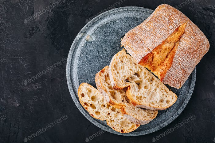 Italian ciabatta bread slices with on stone plate on dark concrete background