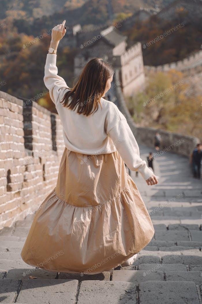 stylish girl visiting the Great Wall of China near Beijing during autumn season
