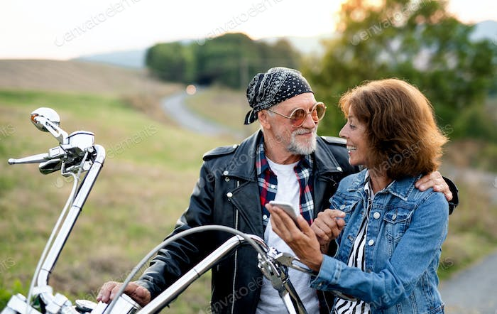 A senior couple travellers with motorbike in countryside, using smartphone.