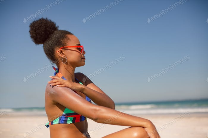 African american woman in bikini applying sunscreen lotion on shoulder at beach