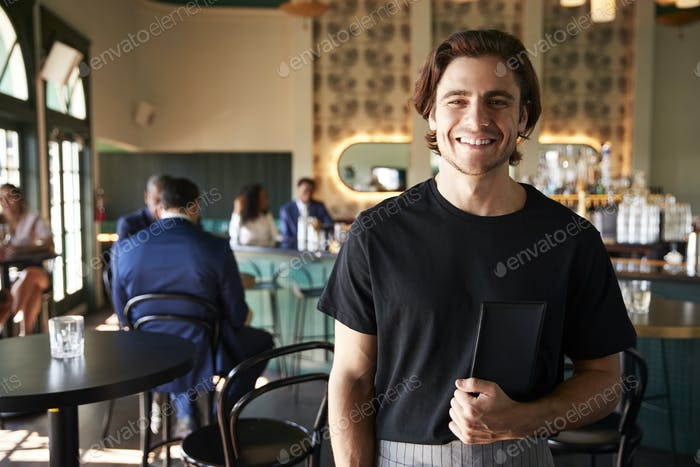 Waiter In Busy Cocktail Bar Of Restaurant With Customers At Camera