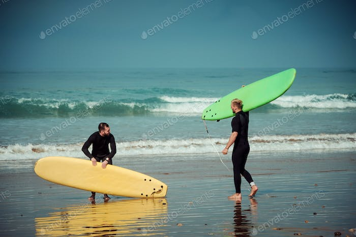 Surfer beginner and instructor on a beach with a surfing boards