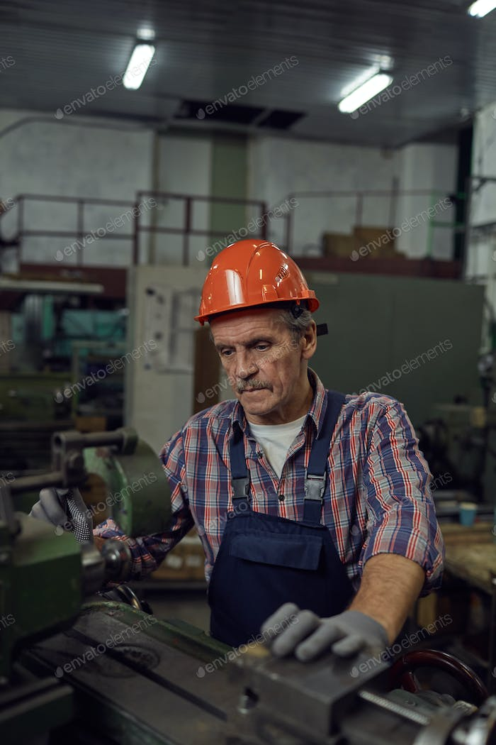 Man cutting metal at lathe