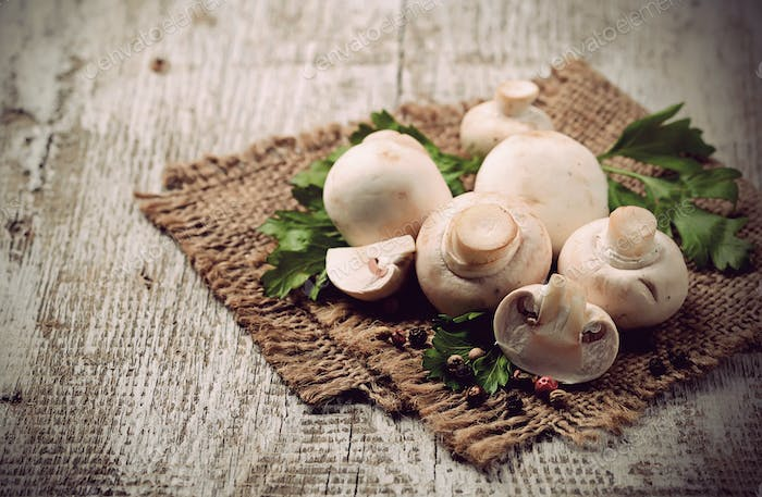 Raw champignon mushroom on wooden background