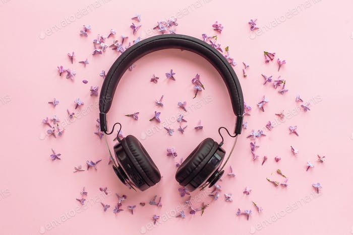 Stylish black headphones on pink background with lilac flowers