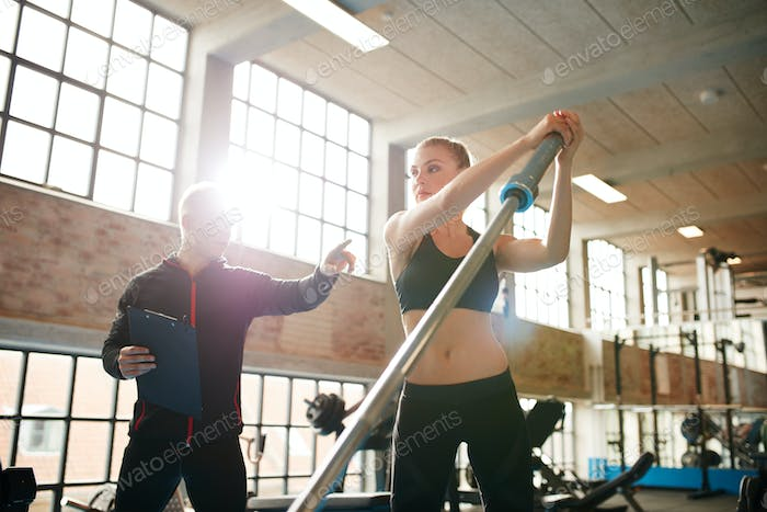 Woman exercising with fitness trainer in gym