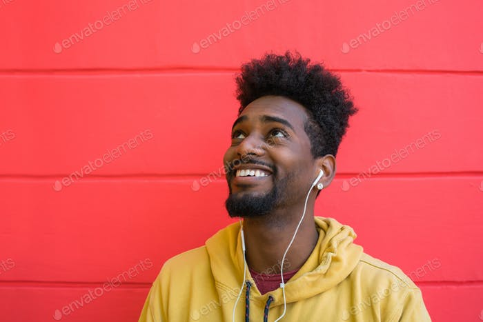 Young afro man listening to music with earphones.