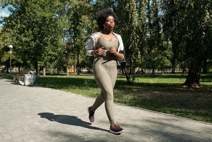 Contemporary young female in activewear jogging in park