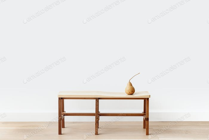 Brown pear on a wooden bench in a white room