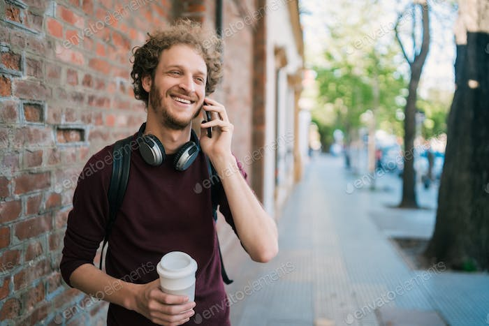 Young man talking on the phone outdoors.