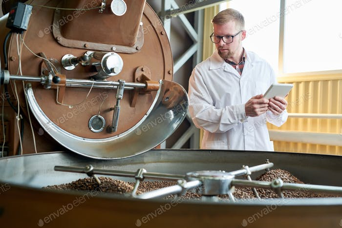 Modern Worker Roasting Coffee at Factory