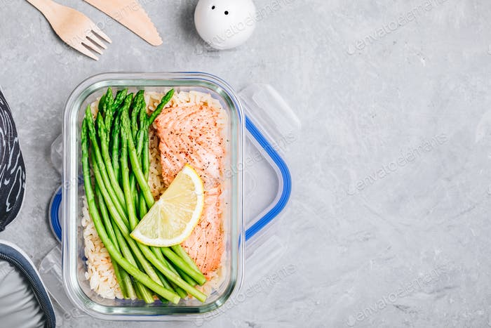 Meal prep lunch box container with baked salmon fish, rice, green asparagus