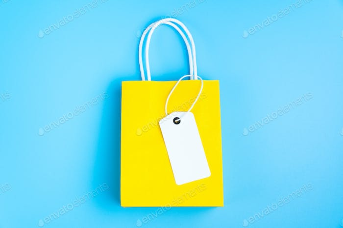 Yellow shopping or gift bag isolated on blue