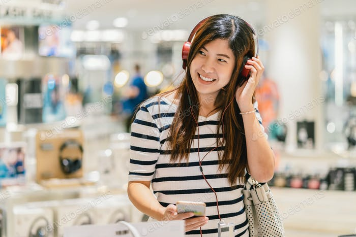 Happy Asian woman listening and testing technology Earphone or headphones in store shop
