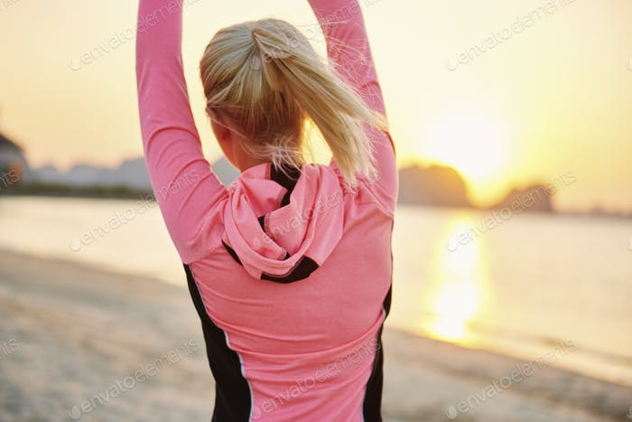 Rear view of woman exercising on the beach