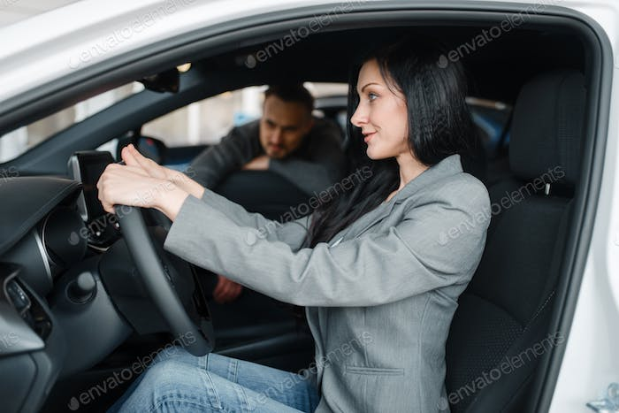 Cheerful couple buying new car in showroom