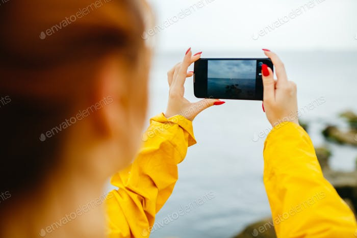 Girl taking photo of ocean