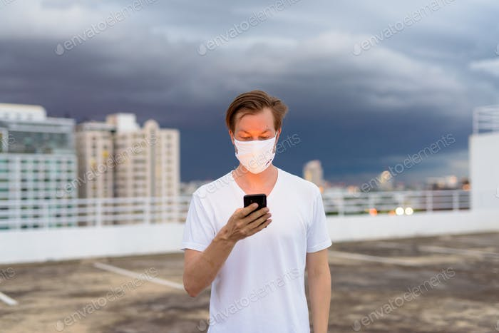 Young man with mask using phone against view of the city during stormy weather outdoors