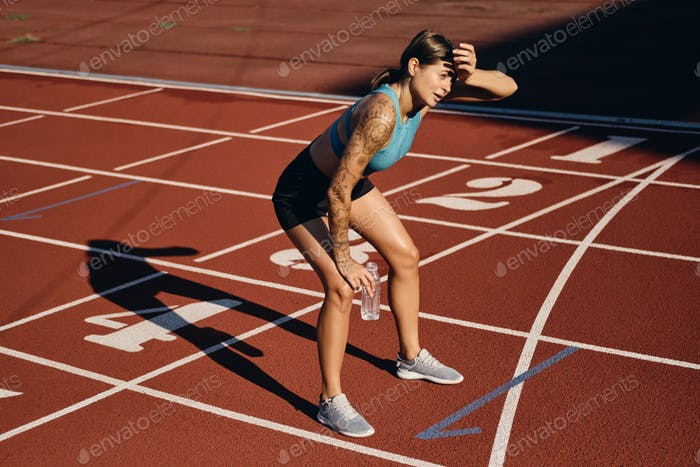 Athlete woman in sportswear with bottle of water tiredly leaning on knees after running on stadium