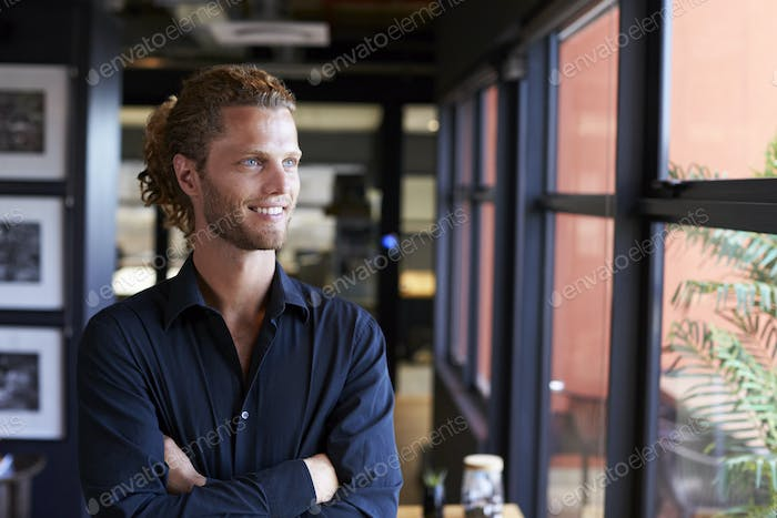 Millennial white male business creative smiling and looking out of the window in an office, waist up