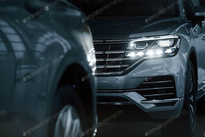 Powerful headlights. Particle view of modern luxury cars parked indoors at daytime