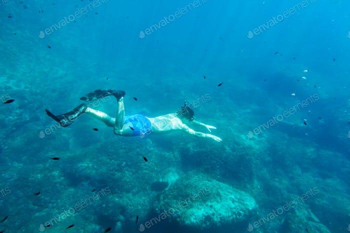 man swim underwater in snorkel