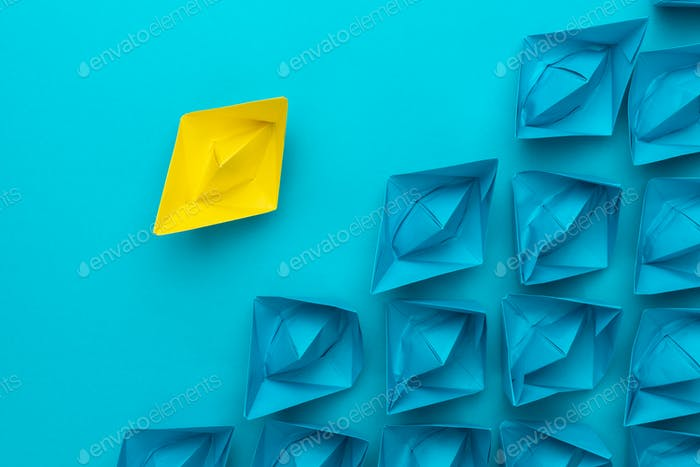 Yellow Paper Ship Out Of The Crowd Concept Over Blue Background