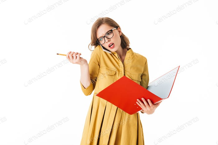 Portrait of busy lady in eyeglasses talking on her cellphone while angrily looking aside