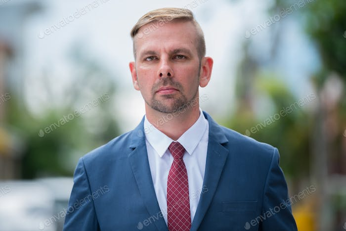 Head shot of businessman with blond hair wearing blue suit outdoors