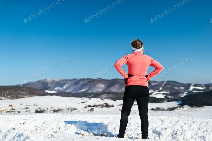 Rear view of senior woman runner resting in winter nature.