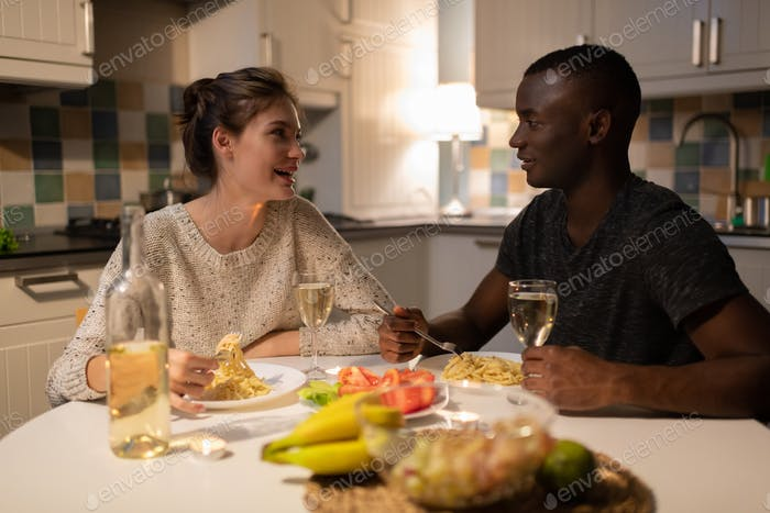Happy multiracial couple eating spaghetti during romantic date at home
