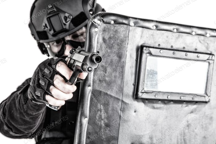 SWAT team fighter aiming pistol from behind shield