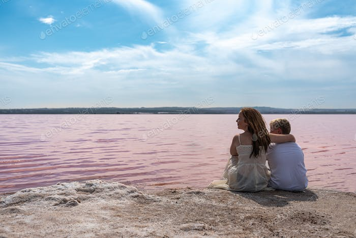 cute teenager brothers sitting on a shore of amazing pink lake